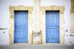 Två blåa dörrar i en sydlig stilbyggnad arkivfoton