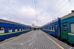 Två blåa drev på plattformen för drevstation i vintern Arkivbilder