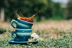 Två blåa keramiska koppar med en färgstänk Arkivfoton