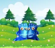 Två blåa monster på bergstoppet med sörjer träd Arkivbild