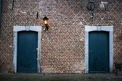Två blåa tvilling- dörrar i en slottdomstolgård royaltyfri fotografi