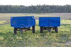 Två blåa vagnar för traktorer är i trädgården i byn arkivfoto