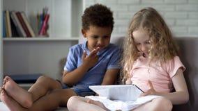 Två blandras- barn som sitter på den hemtrevliga soffan och hållande ögonen på tecknade filmer på minnestavlan arkivbilder