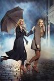 Två blonda damer som kör under regn Arkivfoto