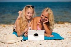 Två blonda kvinnor som har den roliga surfa internet på stranden i sommar Arkivfoto