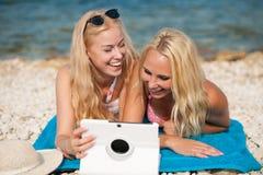 Två blonda kvinnor som har den roliga surfa internet på stranden i sommar Royaltyfri Bild