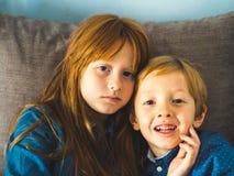 Två blonda lilla ungar i blåa skjortor på soffan royaltyfri bild