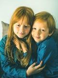 Två blonda lilla ungar i blåa skjortor royaltyfri fotografi