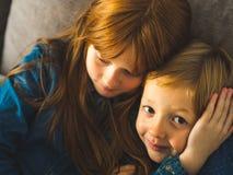 Två blonda lilla ungar i blåa skjortor royaltyfri bild
