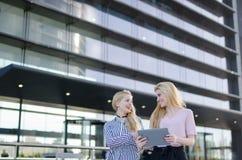 Två blonda studentvänner som skrattar genom att använda mobiltelefonen och minnestavlan Arkivbilder