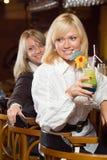 Två blonds på en stångräknare med en coctail Arkivfoto