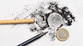 Två blyertspennor och ett euromynt Arkivfoto