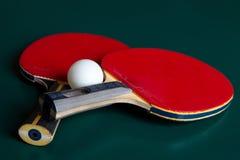 Två bordtennisracket och en boll på en grön tabell royaltyfria bilder