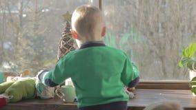 Två bröder är stirriga på fönsterfönsterbrädan på jultid lager videofilmer