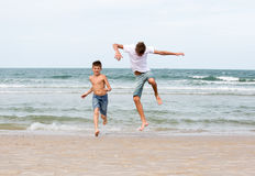 Två bröder av en tonåring som spelar på havet, kamratskapnollan Arkivbilder