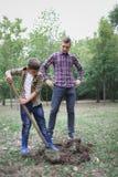 Två bröder en pikjord i en parkera för att plantera det unga trädet Familjarbete, höstdag Royaltyfria Bilder