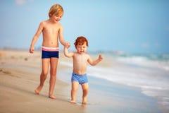 Två bröder, gulliga ungar som har gyckel på den sandiga stranden arkivbilder