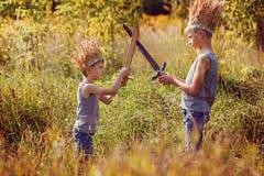 Två bröder har en krona från torrt gräs på huvudet och svärden i händer Glädje- och lekbegrepp Fotografering för Bildbyråer
