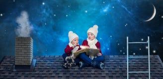 Två bröder sitter på julnatt på taket och läser en bok med sagor I förväntan av julmirakel royaltyfri foto