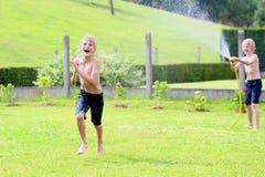 Två bröder som spelar med vatten, vattnar med slang i trädgården Fotografering för Bildbyråer