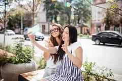 Två bra seende tunna flickor med långt mörkt hår, iklädd tillfällig vagel, sitter på bänken och tar en selfie, arkivbilder