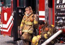 Två brandmän tar ett avbrott, når de har slagits en husbrand arkivbilder