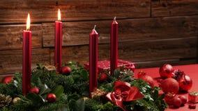 Två brinnande röda stearinljus på en traditionell adventkrans med festlig garnering lager videofilmer
