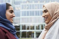 Två brittiska muslimska kvinnavänner som möter utanför kontor Arkivfoto