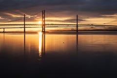 Två broar mot inställningssolen och havet Royaltyfri Fotografi