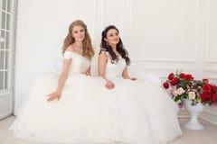 Två brudar i bröllopsklänningar sitter på en vit soffa arkivfoto