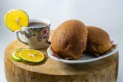 Två bruna bröd på en platta och en kopp av varmt citronte förläggas på ett trämattt med en isolerad vit bakgrund royaltyfria foton