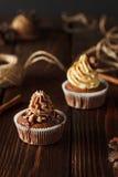 Två bruna chokladmuffin på wood bakgrund Royaltyfri Foto