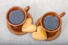 Två bruna keramiska koppar kaffe, hemlagade kakor Fotografering för Bildbyråer