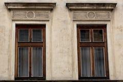 Två bruna träWindows på fasaden av det gammalt smutsar ner huset arkivfoto