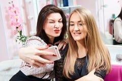 Två brunettflickor och en blondin gör en selfie i en skönhetsalong royaltyfria bilder