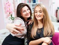 Två brunettflickor och en blondin gör en selfie i en skönhetsalong royaltyfri fotografi