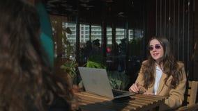 Två brunettkvinnor talar i öppen terrass i kafé i vårtid stock video