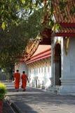 Två buddistiska munkar promenerar den huvudsakliga korridoren av Wat Benchamabophit i Bangkok (Thailand) royaltyfri foto