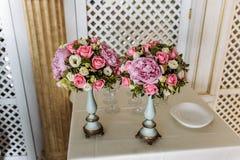 Två buketter av rosor och pioner i eleganta vaser på en ljus bakgrund royaltyfria foton