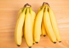 Två Bunces av gula bananer på den Wood tabellen Royaltyfri Fotografi