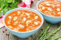 Två bunkar av tomatsoppa med pasta, vita bönor och rosmarin fotografering för bildbyråer