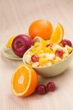 Två bunkar med fruktsallad på trätabellen med halva av apelsinen Royaltyfri Bild