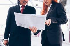 Två businesspeople som håller ögonen på tidningen och talar om avbrott arkivfoto