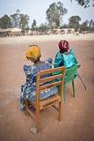 Två bydamer håller ögonen på en fotbollsmatch på en skola i Uganda Royaltyfri Fotografi