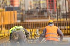 Två byggmästare i guling och apelsin på konstruktionsplatsen Arkivfoto
