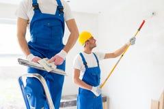 Två byggmästare med målninghjälpmedel som reparerar rum Royaltyfria Bilder