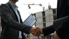 Två byggmästare skakar händer stock video