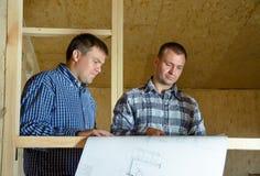 Två byggmästare som diskuterar ett byggnadsplan Arkivbild