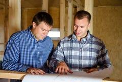Två byggmästare som diskuterar ett byggnadsplan Royaltyfria Foton