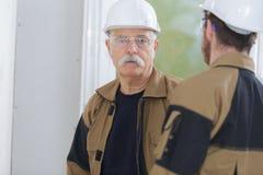Två byggmästare som har konversation royaltyfri fotografi